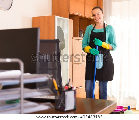 Smiling young woman in apron cleaning office room - stock photo