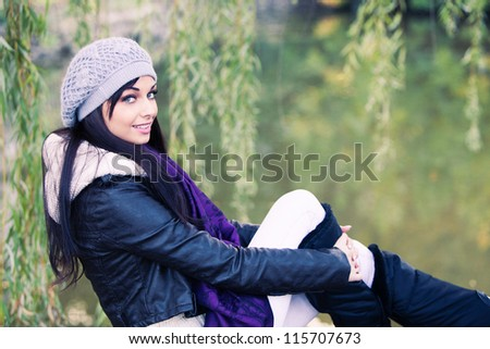 smiling young woman in autumn casual clothes portrait by the lake - stock photo