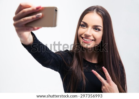 Smiling young woman in black dress making selfie photo on smartphone isolated on a white background - stock photo