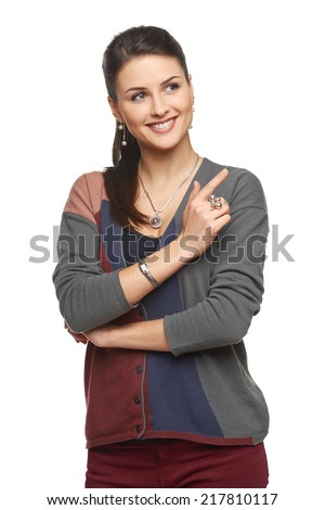 Smiling young woman in cardigan pointing at blank copy space, looking away, over white background - stock photo