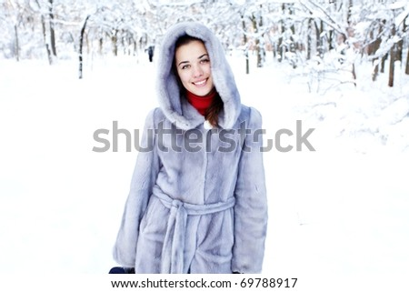 smiling young woman in fur coat outdoors - stock photo