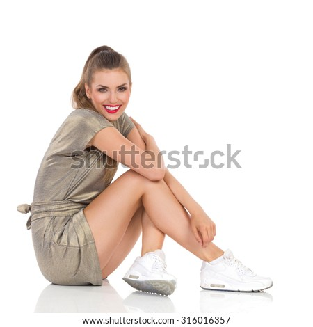 Smiling young woman in gold mini dress and white sneakers sitting on a floor and looking at camera. Full length studio shot isolated on white. - stock photo