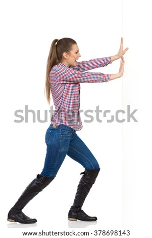Smiling young woman in jeans, black boots and lumberjack shirt pushing a white wall. Side view, full length studio shot isolated on white. - stock photo