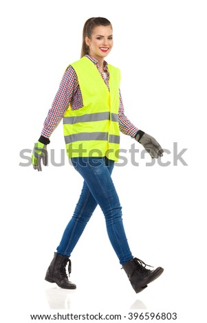 Smiling young woman in lime green reflective vest, protective gloves, jeans, boots and lumberjack shirt walking. Full length studio shot isolated on white. - stock photo