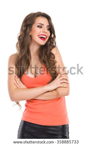 Smiling young woman in orange shirt with sexy neckline standing with arms crossed and looking away. Waist up studio shot isolated on white. - stock photo