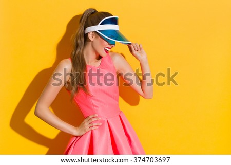 Smiling young woman in pink dress and blue sun visor posing in sunlight and looking away. Three quarter length studio shot on yellow background. - stock photo