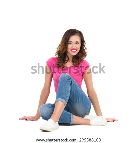 Smiling young woman in pink shirt and jeans sitting on the floor. Full length studio shot isolated on white. - stock photo