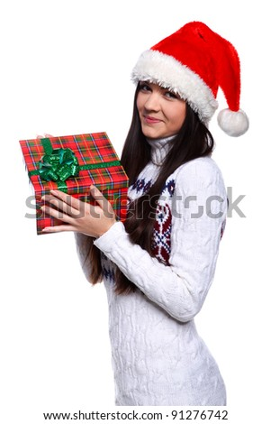 Smiling young woman in red Christmas hat at white background with gifts - stock photo