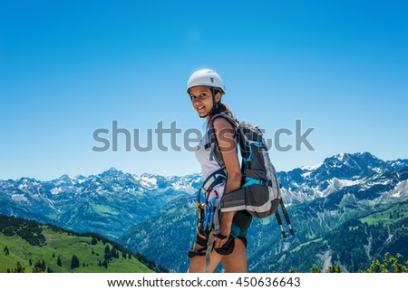 Smiling young woman in short pants, shirt, hiking backpack and helmet standing in foreground of mountain scene with copy space - stock photo