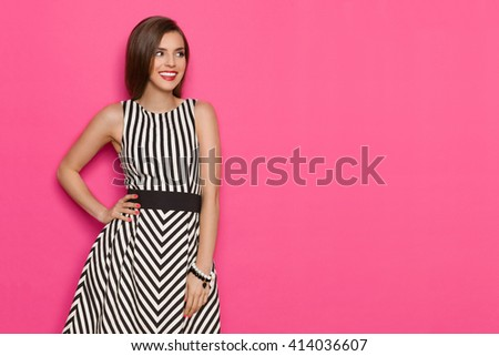 Smiling young woman in striped dress holding hand on hip and looking away at copy space. Three quarter length studio shot on pink background. - stock photo