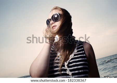 Smiling young woman in sunglasses talking on the phone and sun shines behind her back. - stock photo