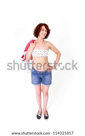 Smiling young woman in swimsuit and shorts with bag - stock photo