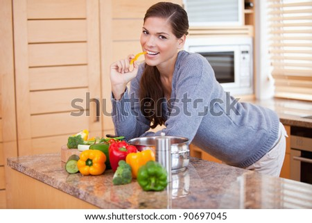 Smiling young woman in the kitchen with vegetables - stock photo