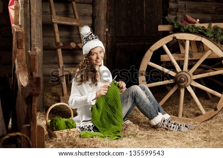 Smiling young woman in the village barn with knitting in hand - stock photo