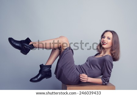 Smiling young woman in trendy boots and dress posing in studio. Casual wear. - stock photo