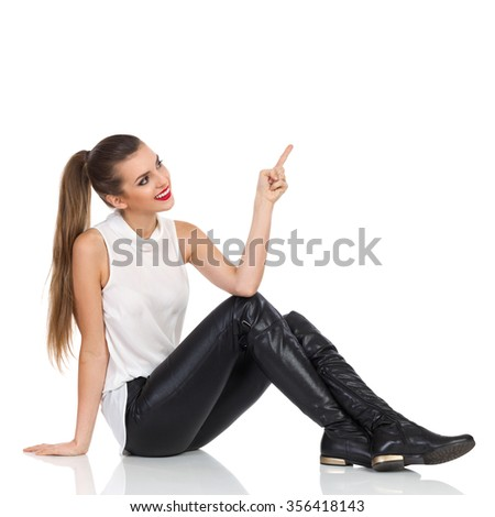 Smiling young woman in white shirt, black leather trousers and boots sitting on a floor, pointing up and looking. Full length studio shot isolated on white - stock photo