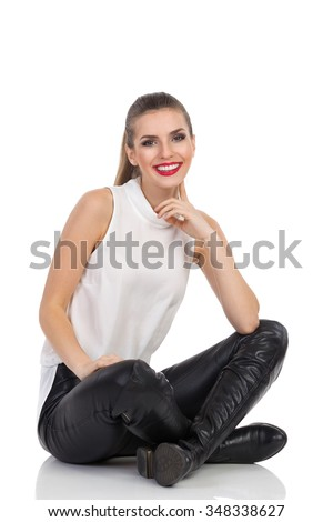 Smiling young woman in white shirt, black leather trousers and boots sitting on a floor with legs crossed, holding finger on chin and looking at camera. Full length studio shot isolated on white. - stock photo