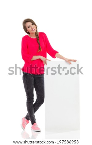 Smiling young woman is standing close to blank placard. Full length studio shot isolated on white. - stock photo