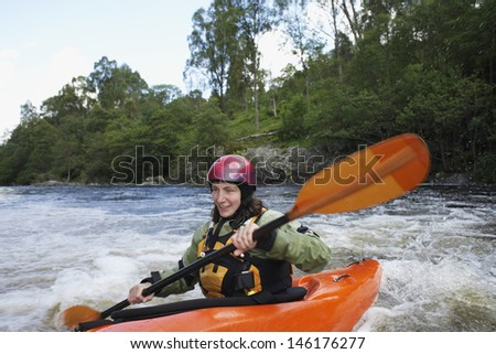 Smiling young woman kayaking in the river - stock photo