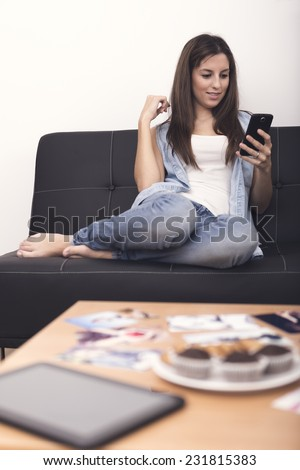 Smiling young woman looking at her smart phone while text messaging at home  - stock photo