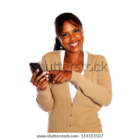 Smiling young woman looking at you and sending a message by cellphone against white background - stock photo