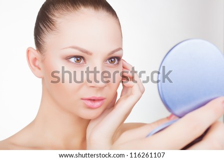 Smiling young woman looking in the mirror on a light background - stock photo