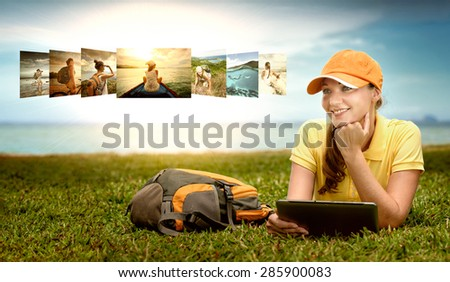 Smiling young woman lying on the lawn with backpack looking at her traveling images in the pad Sharing photo in social media network concept - stock photo