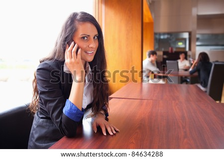 Smiling young woman making a phone call while her coworkers are in a meeting - stock photo