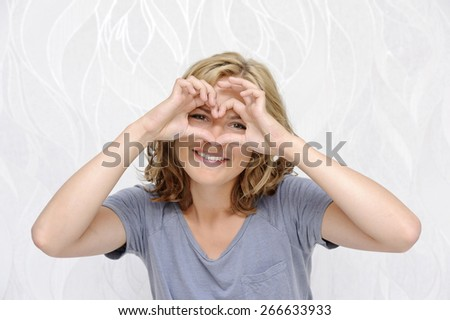 Smiling young woman making heart with fingers - stock photo