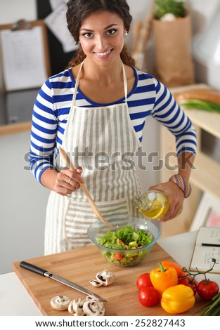 Smiling young woman  mixing fresh salad, standing near desk - stock photo