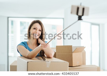 Smiling young woman moving in her new house and taking selfies with a selfie stick - stock photo