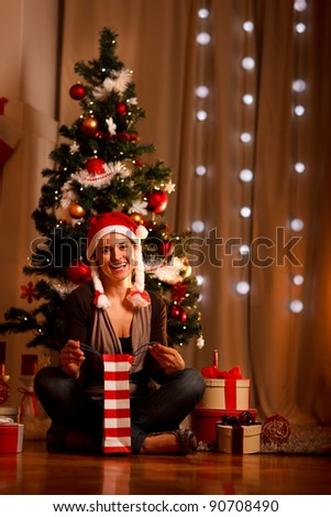 Smiling young woman near Christmas tree opening Christmas present - stock photo