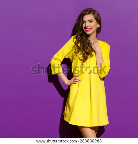 Smiling Young Woman On A Purple Background. Three quarter length studio shot on violet background. - stock photo
