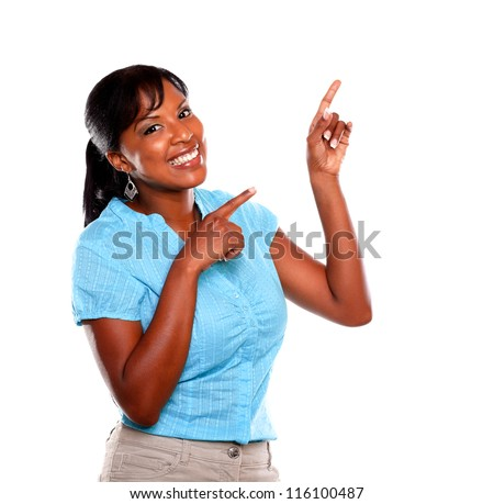 Smiling young woman on blue blouse pointing up and looking at you on isolated background - copyspace - stock photo