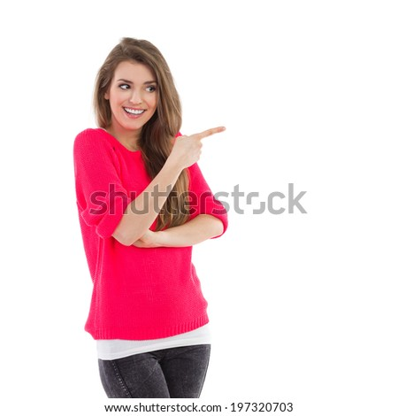 Smiling young woman pointing and looking at empty space. Waist up studio shot isolated on white. - stock photo