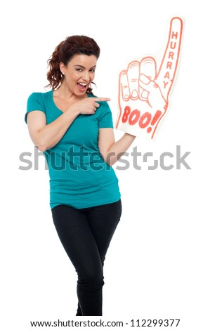 Smiling young woman pointing at large foam hand isolated against white background - stock photo