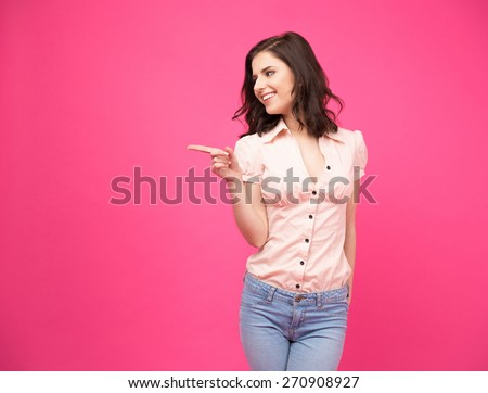 Smiling  young woman pointing finger away over pink background. Wearing in jeans and shirt - stock photo