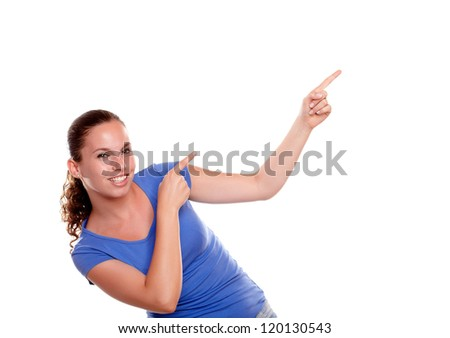 Smiling young woman pointing to her left up while is looking at you standing over white background - copyspace - stock photo