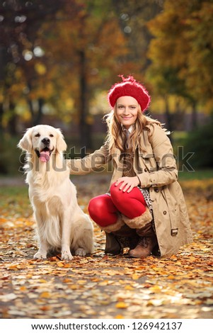 Smiling young woman posing with a labrador retriever dog out in a park - stock photo