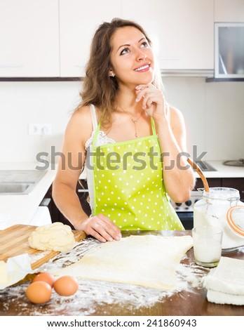 Smiling young woman preparing dough at kitchen - stock photo
