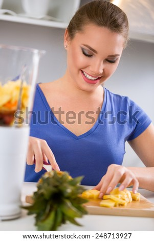 Smiling young woman preparing healthy food cutting pineapple - stock photo