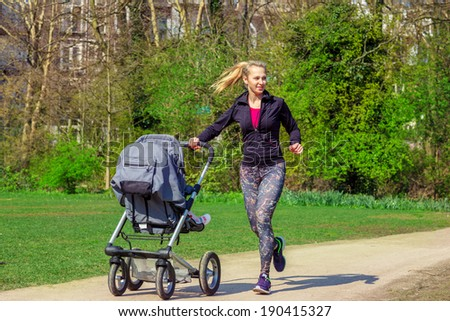 Smiling young woman pushing baby buggy while exercising in a park - stock photo