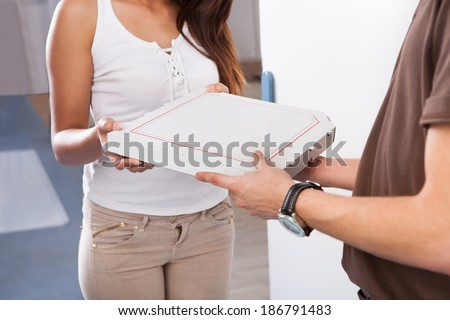 Smiling young woman receiving pizza from delivery man at home - stock photo