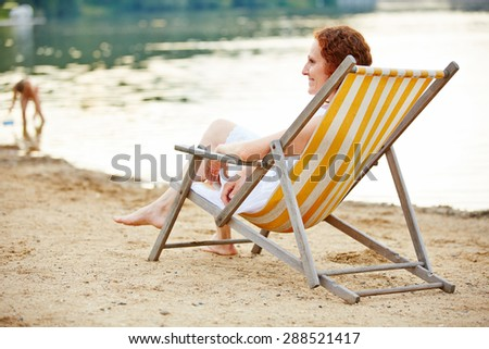 Smiling young woman relaxing on beach in deck chair in summer - stock photo