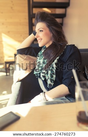 Smiling young woman relaxing on the sofa in a lounge bar - stock photo