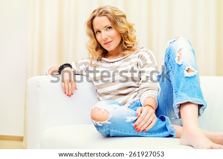 Smiling young woman resting at home on a sofa. Interior. - stock photo