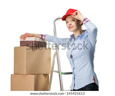 Smiling young woman resting near a pile of boxes, isolated on white - stock photo