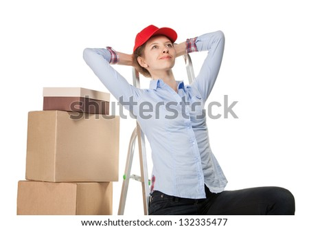 Smiling young woman resting near a pile of boxes on white background - stock photo