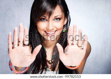 smiling young woman show stop sign with her hands, studio shot - stock photo