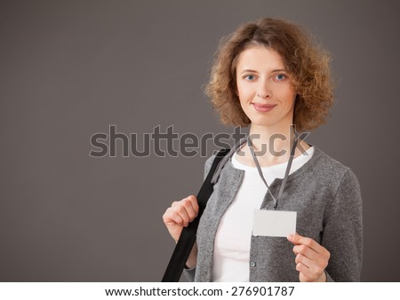 Smiling young woman showing badge, gray background - stock photo